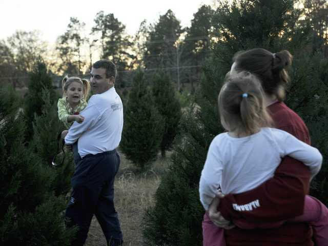 Gene Sherry, left, helps family friend Marci Cochran and her children  Cameron, 5, left, and Chloe, 3, pick out the perfect tree at Wiggins  Christmas Tree ... - Christmas Tree Farmer Robert Wiggins Helps Families Find The Perfect